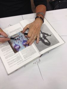 The hands of Alice Cooper signing my book and CD cover